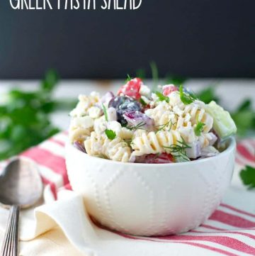 A Greek pasta salad in a bowl with a spoon at the side