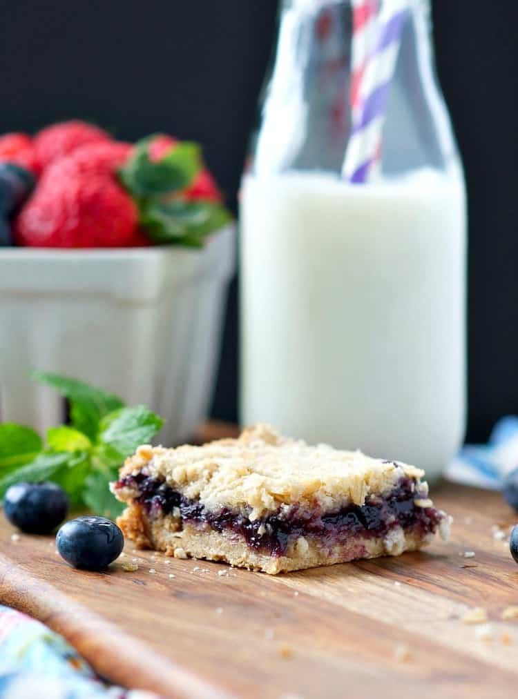 A close up of blueberry muffin bars with milk in the background