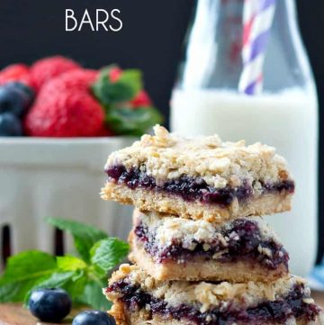 Blueberry muffin bars stacked on top of each other with milk in the background