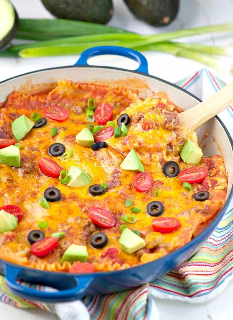A Mexican Skillet lasagna in a blue skillet topped with avocado, olives and tomatoes