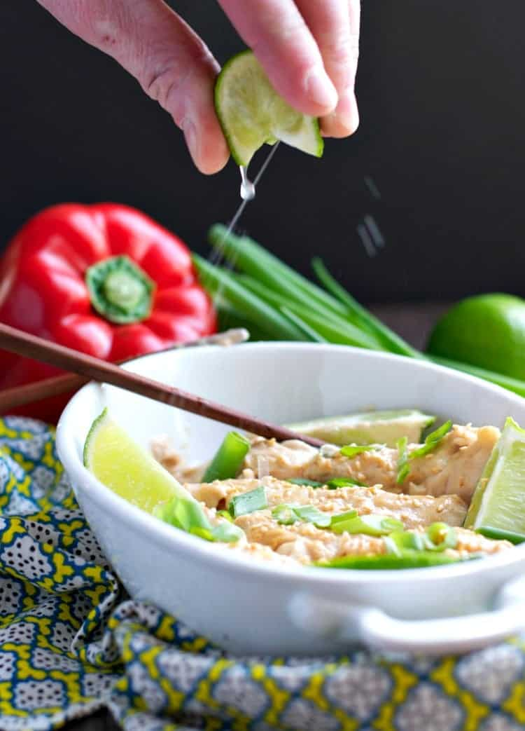 A hand squeezing fresh lime juice over peanut chicken