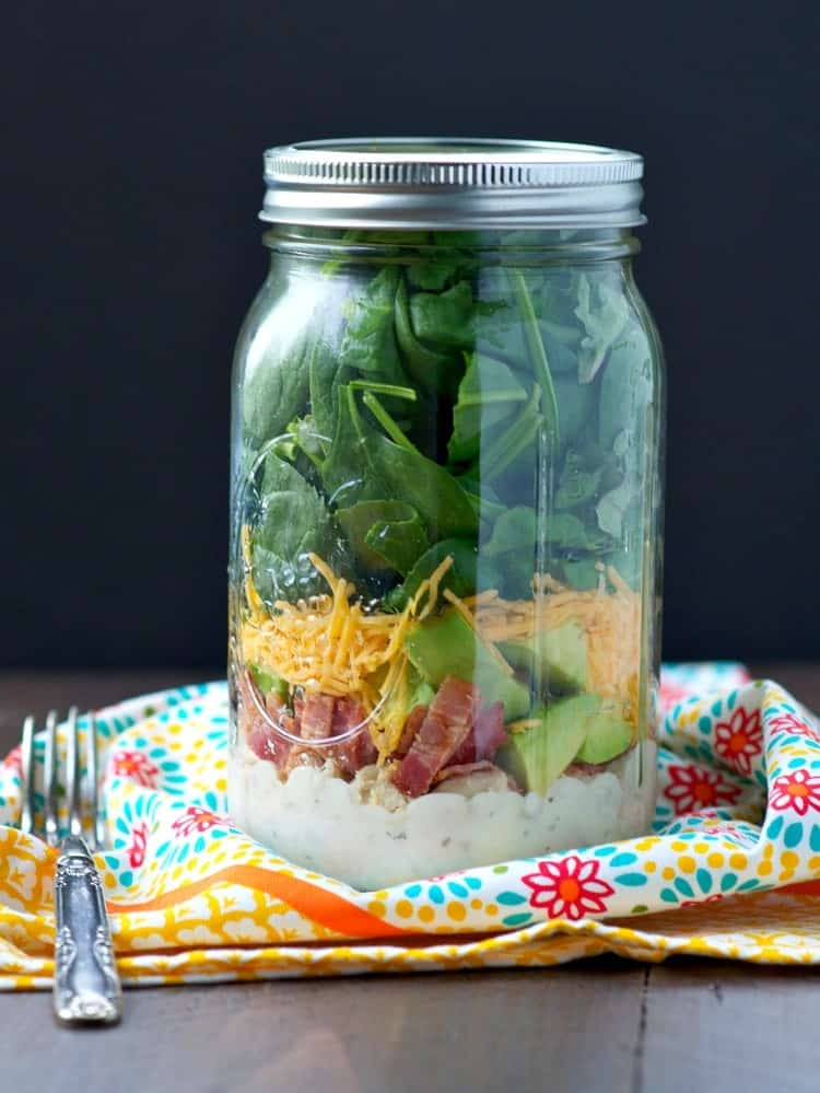 A close up of a chicken and bacon ranch salad in a mason jar