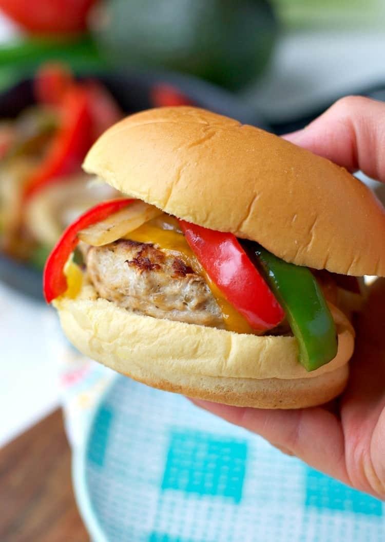 A hand holding a chicken fajita burger