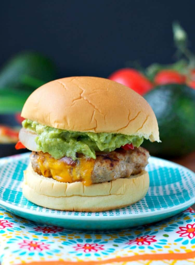 A chicken fajita burger with cheese dripping down the side sitting on a blue plate