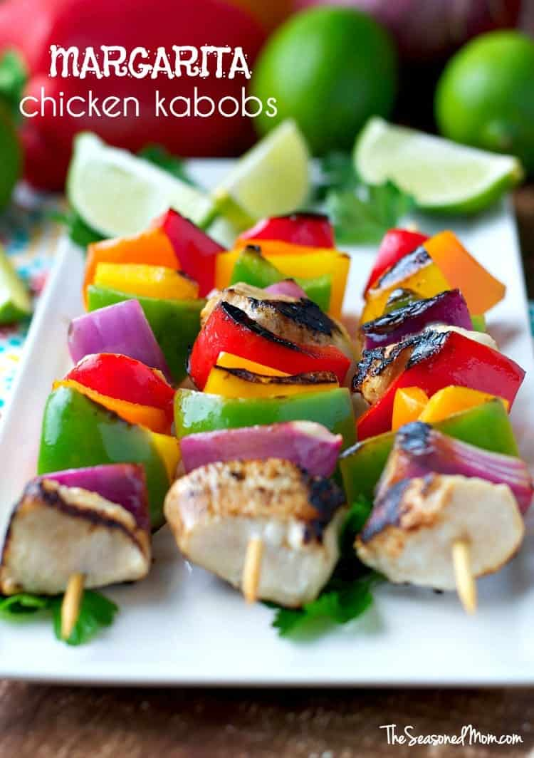A close up of chicken kabobs on a white plate