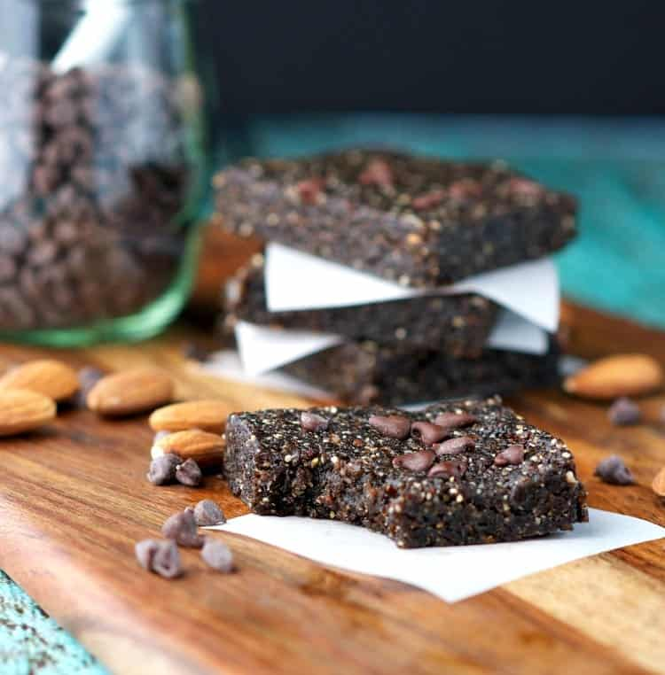 Homemade energy bars on a wooden surface and one with a bite out