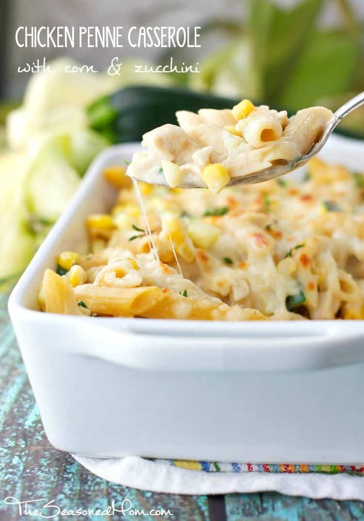 A close up of a chicken pasta casserole with a serving spoon lifting up a spoonful