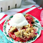 Healthy strawberry crisp on a plate with a scoop of vanilla ice cream