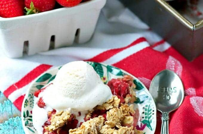 Strawberry crisp on a plate with ice cream and strawberries in the background