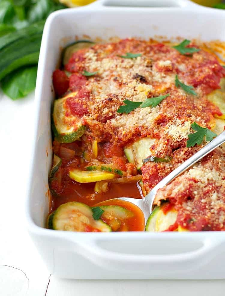 A baking dish with squash and zucchini gratin and a serving spoon