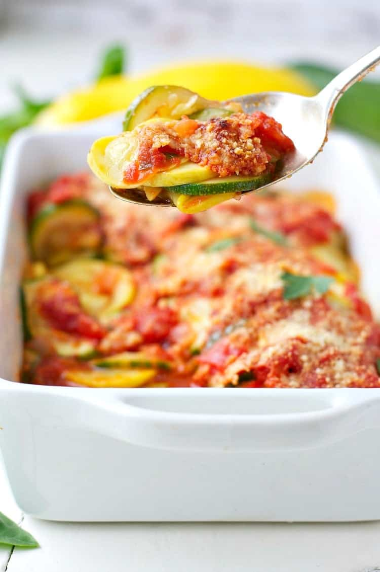 A spoon picking up some zucchini gratin from a baking dish