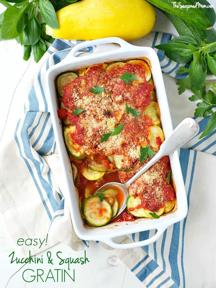 An overhead shot of zucchini gratin in a baking dish with a servings spoon