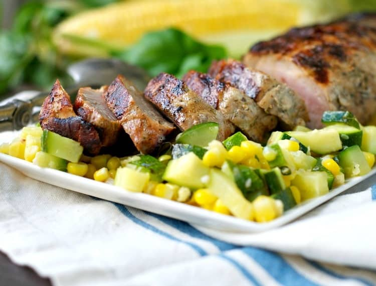 A close up of sliced boneless pork tenderloin with zucchini and corn