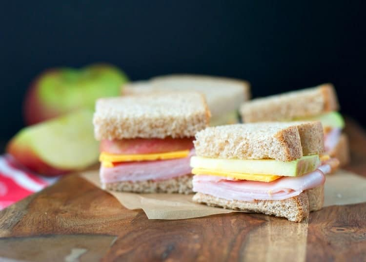 Picnic sandwiches sitting on a wooden surface