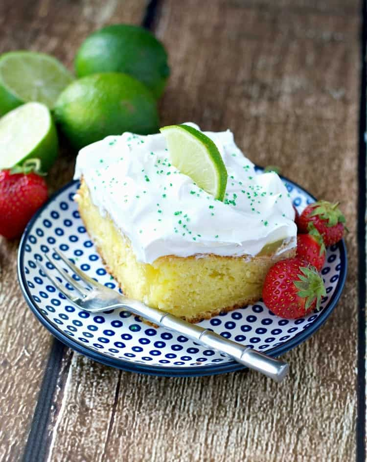 Slice of easy margarita poke cake on a plate with fresh berries and lime.