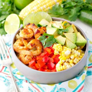 Bowl of marinated shrimp and summer vegetables in a bowl with quinoa and diced avocado