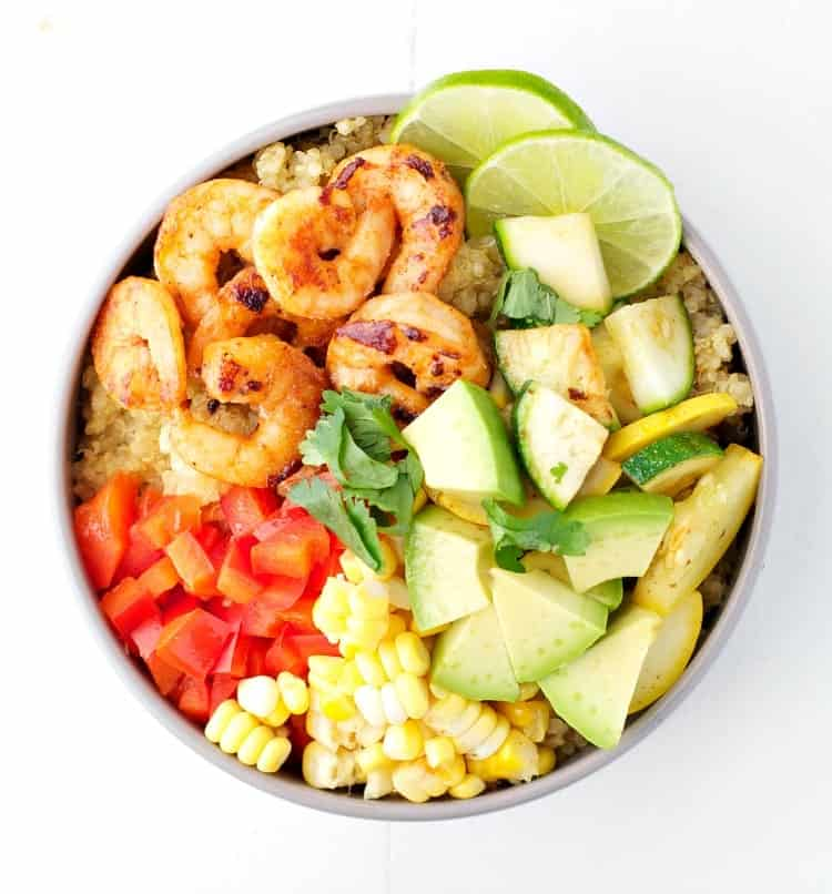An overhead shot of marinated shrimp in a bowl with quinoa and veggies