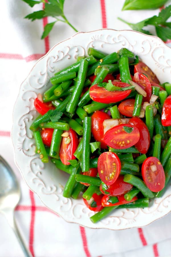 Overhead shot of fresh string bean salad in a white bowl with tomatoes