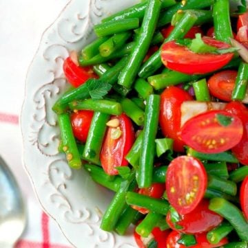 Close overhead shot of green bean salad with tomatoes in a white bowl