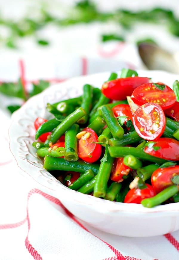 Front shot of a bowl of Green Bean Salad with cherry tomatoes