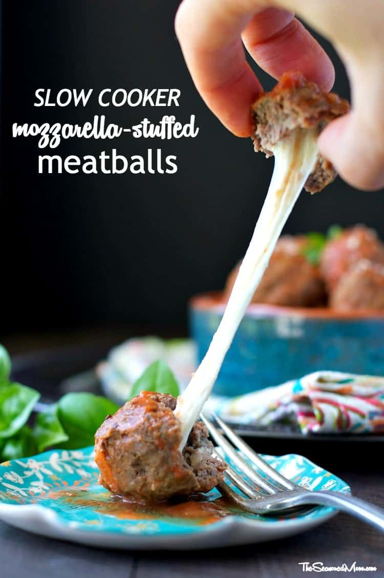 Mozzarella stuffed meatballs on a plate with cheese oozing out