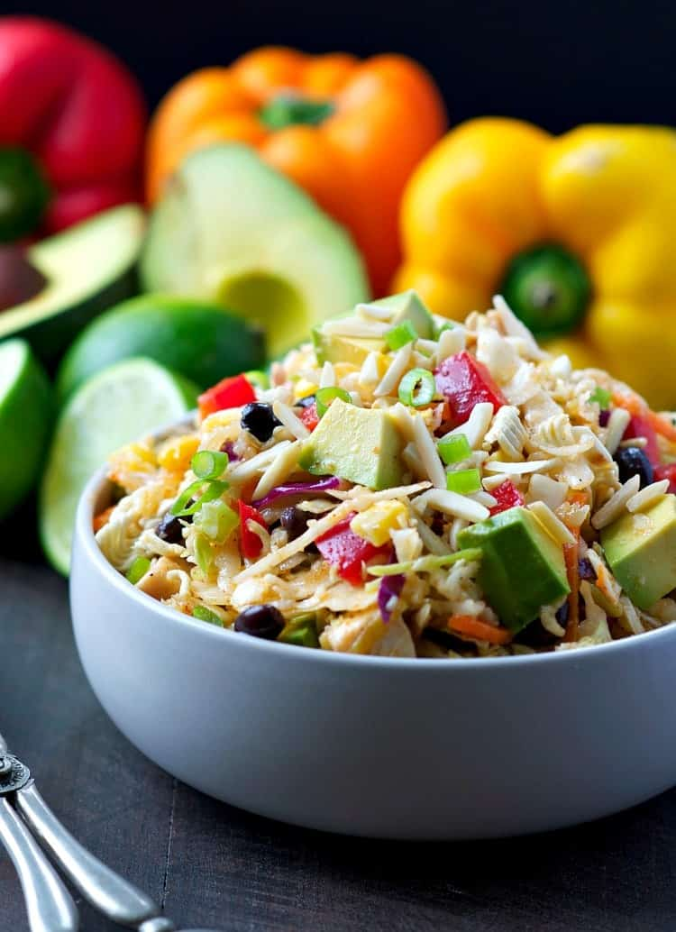 A close up of a chicken ramen salad in a bowl with peppers and avocados in the background