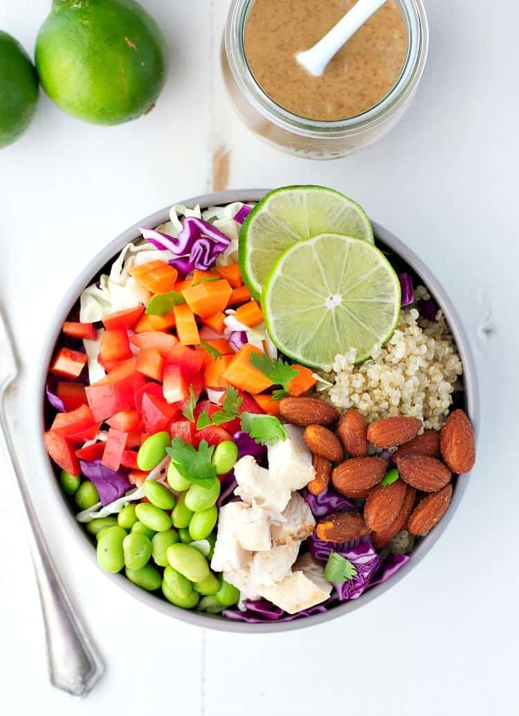 An overhead shot of a chicken and quinoa bowl topped with lime wedges