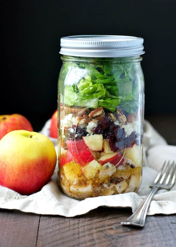 A close up of a mason jar salad with apples at the side