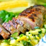 Close up shot of Garlic and Herb Boneless Pork Tenderloin over a bed of corn and zucchini