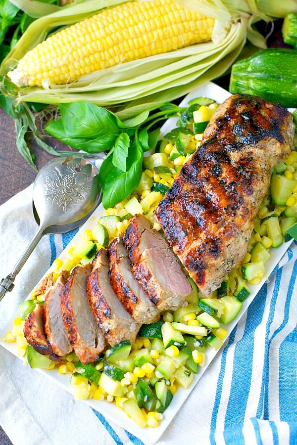Long overhead shot of sliced garlic and herb pork tenderloin served with sauteed zucchini and corn