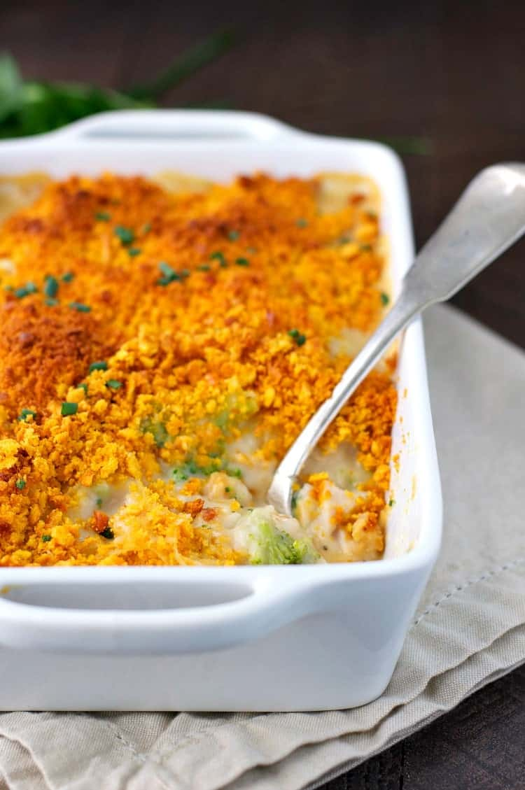 A side shot of cheddar Crusted Chicken and Broccoli Casserole in a white dish