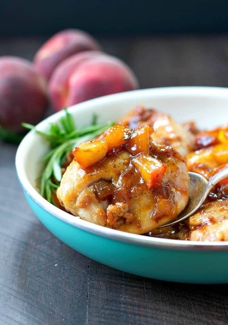 A close up of peach glazed chicken in a bowl