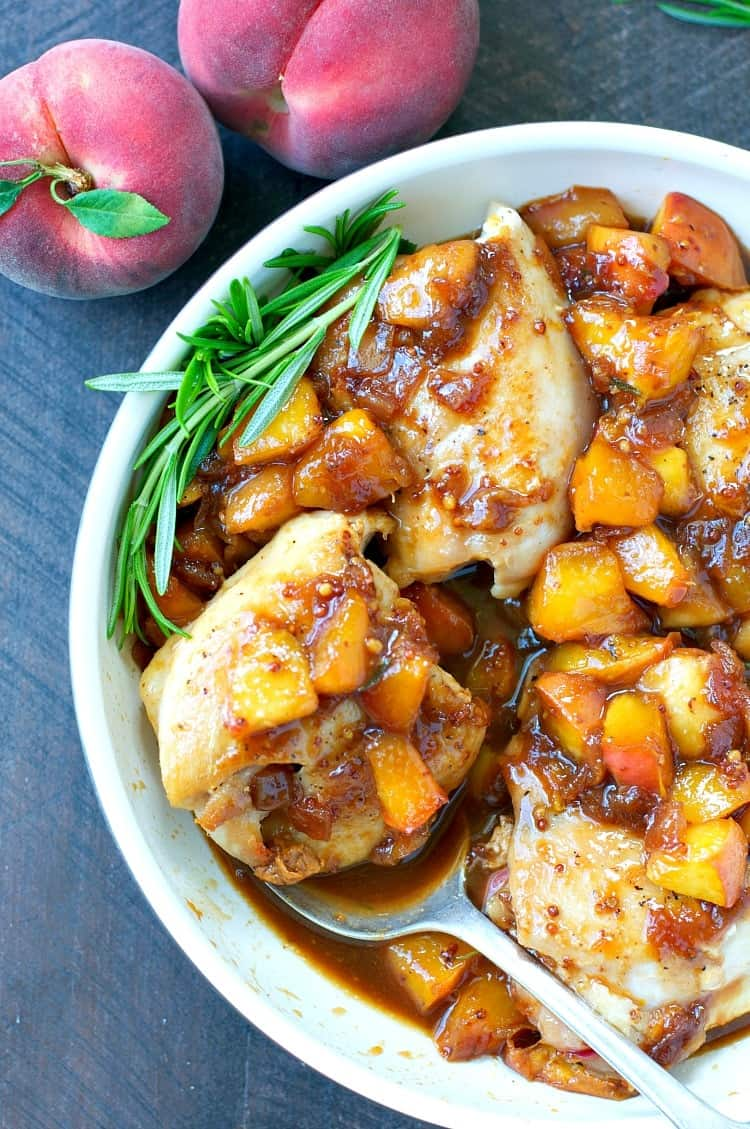 An overhead shot of peach glazed chicken in a large bowl