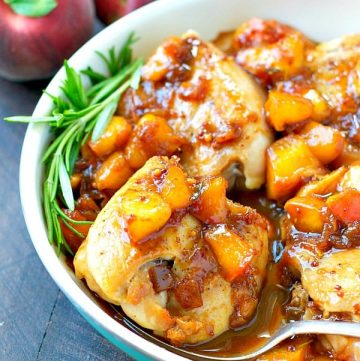 A close up of peach glazed chicken in a blue skillet