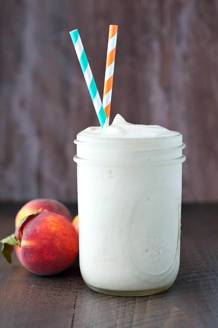 A photo of a glass jar filled with a peaches and cream protein smoothie and two straws