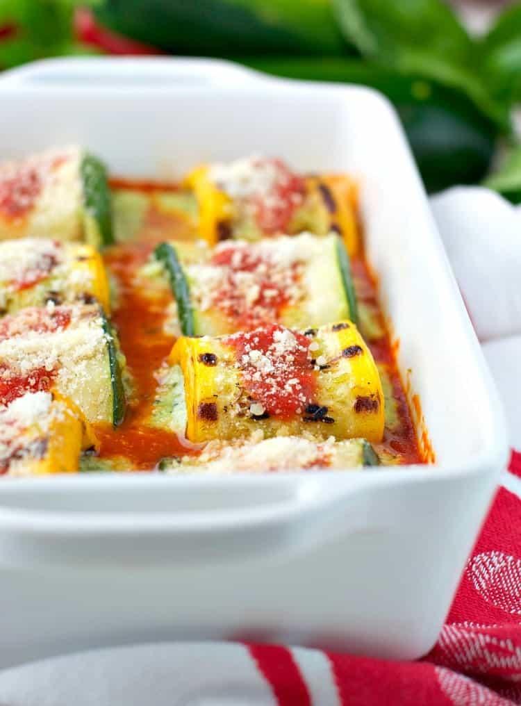 A close up of pesto zucchini lasagna roll ups in a white casserole dish