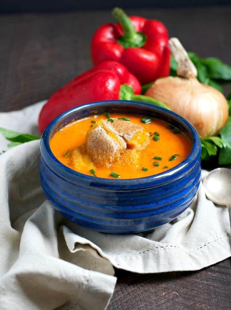 A blue bowl filled with roasted red pepper soup and cheese croutons