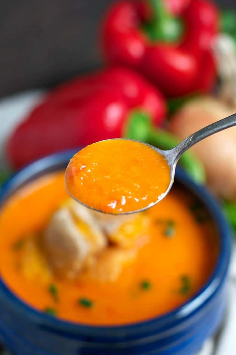 A spoon scooping up some roasted red pepper soup from a bowl