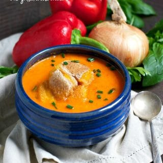 Roasted red pepper soup in a blue bowl topped with croutons