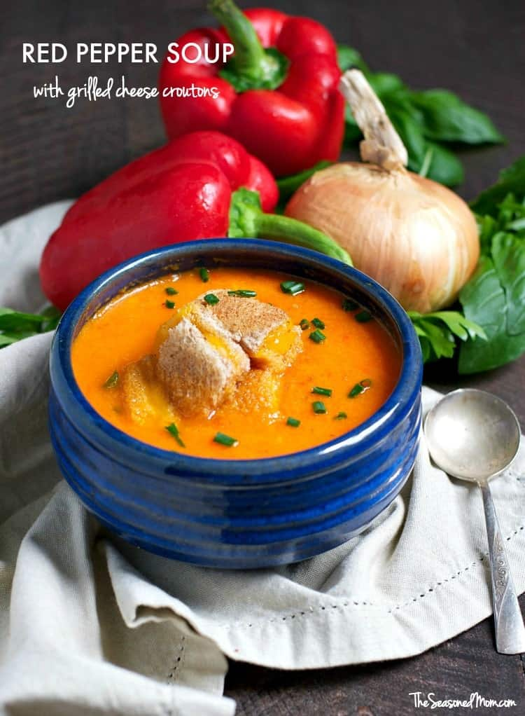 Roasted red pepper soup in a blue bowl topped with cheese croutons and vegetable in the background