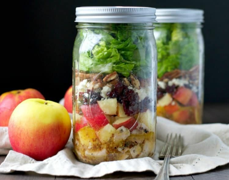 A side shot of mason jar salads with apples and a fork at the side