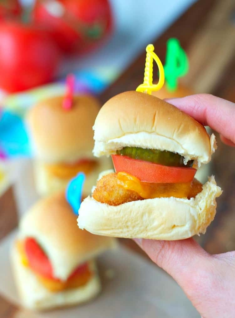 A close up of a hand holding chicken nugget sliders