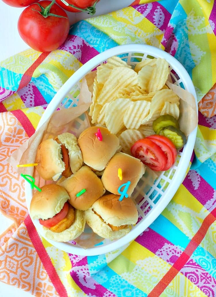 Chicken nugget sliders in a basket with chips and sliced tomatoes and pickles