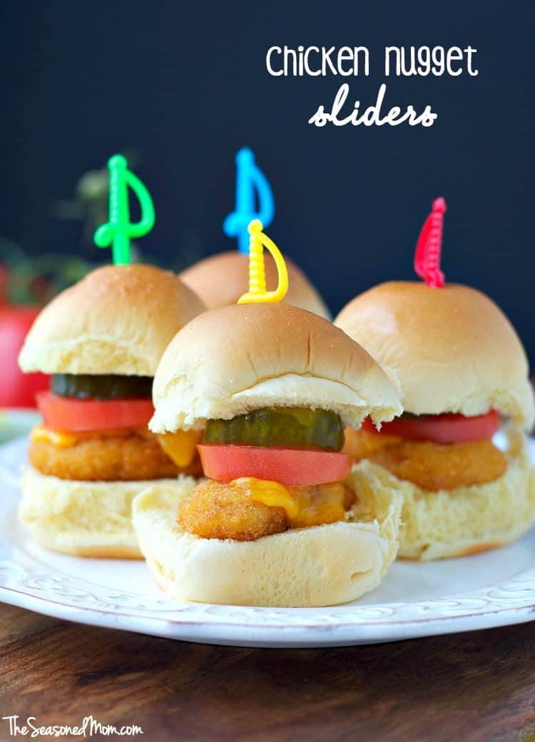 Three chicken nugget sliders on a plate with tomato and pickles