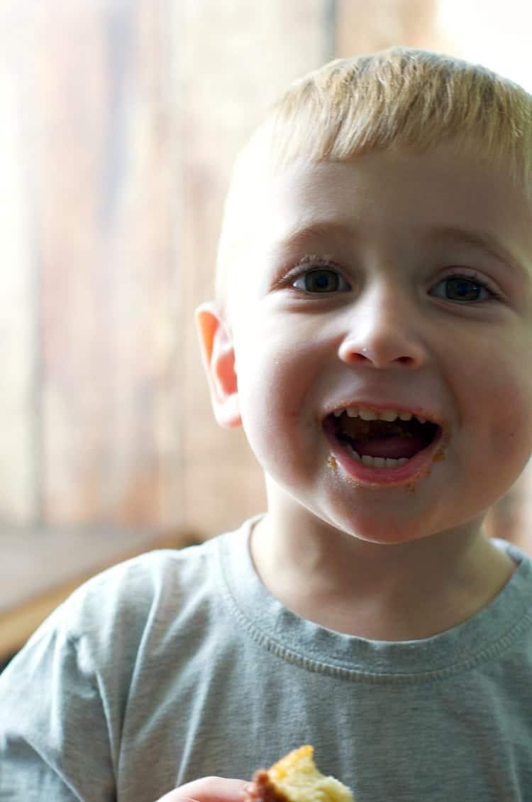 A boy smiling eating cinnamon sugar puff muffins