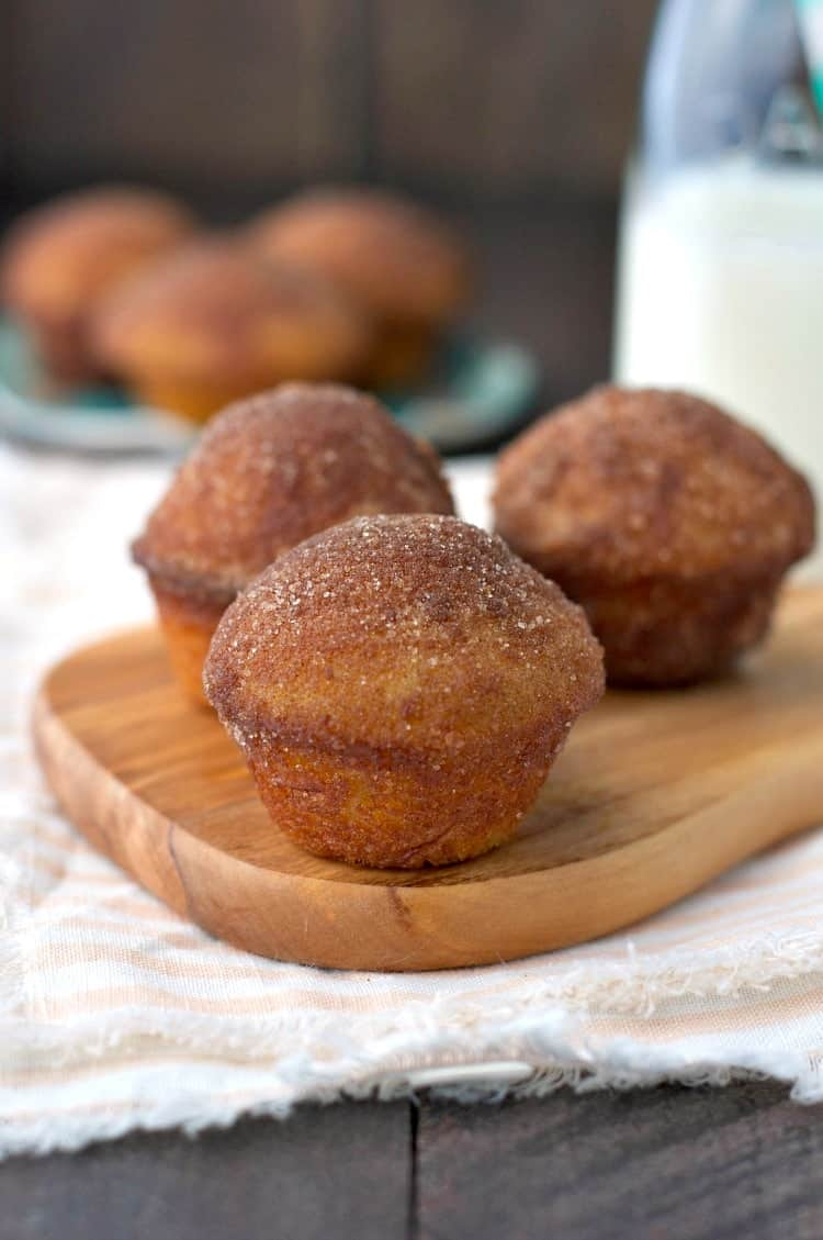 Three cinnamon sugar puff muffins on a wooden chopping board with more in the background