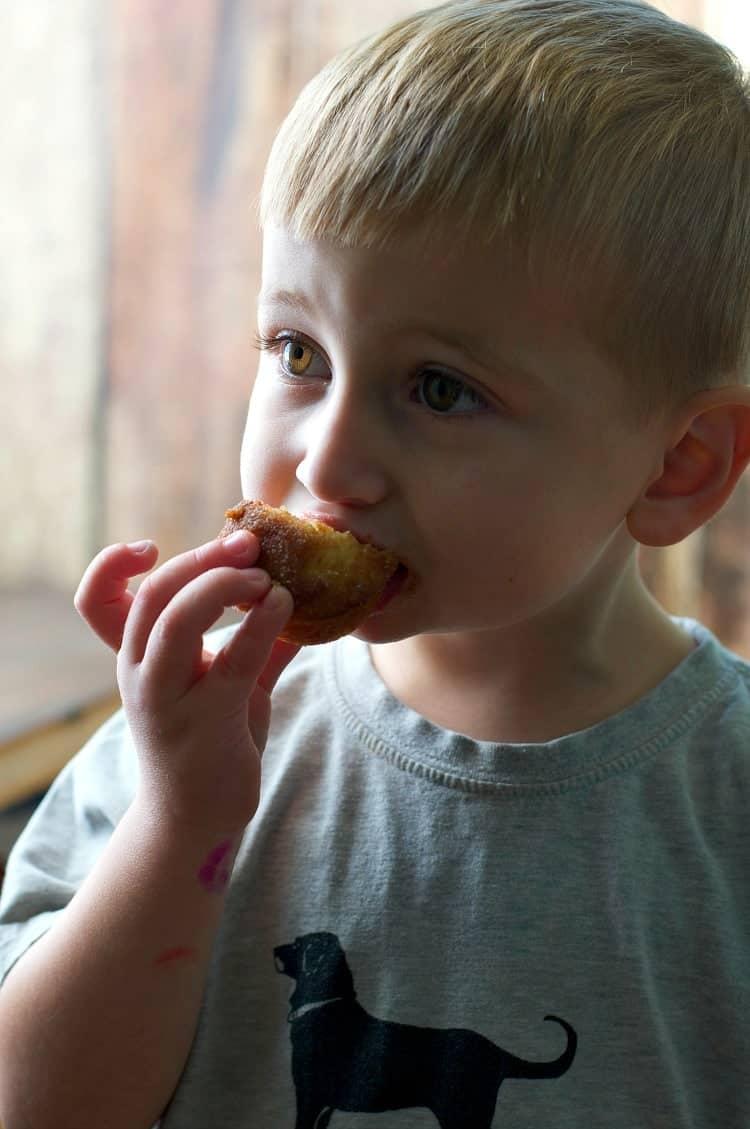 A little boy eating cinnamon sugar puff muffins