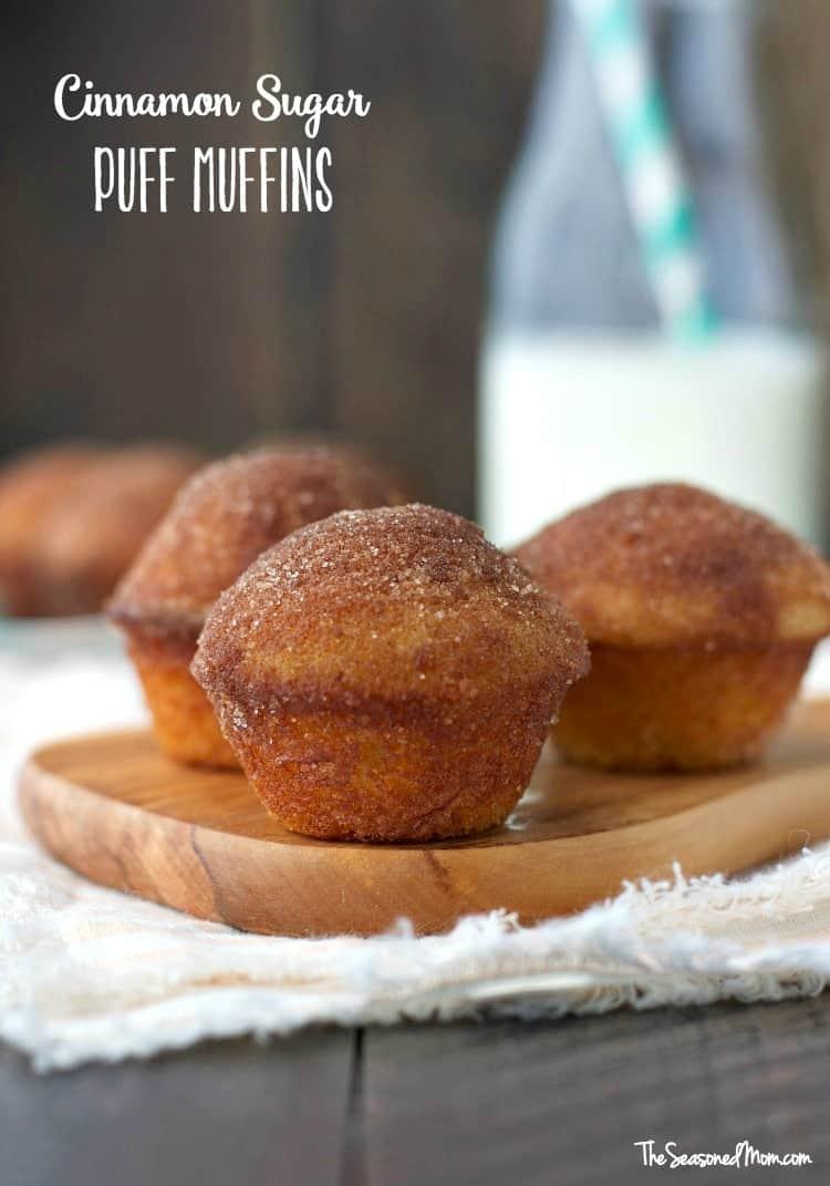 Three cinnamon sugar puff muffins on a wooden chopping board