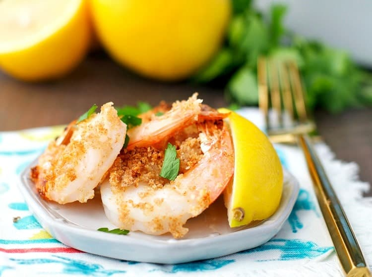 A close up of garlic butter shrimp on a plate with lemon wedges