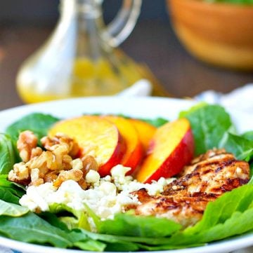 A grilled chicken and nectarine salad on a plate with walnuts
